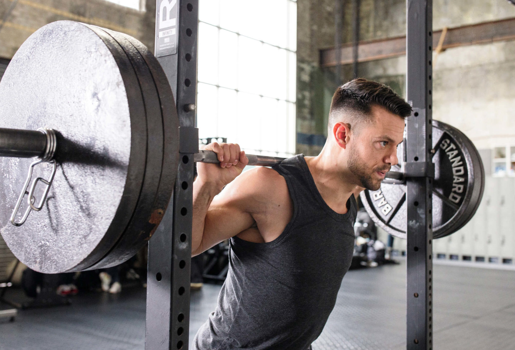 A picture of a Caliber online personal training client. A muscular male is wearing a grey vest performing a barbell back squat in a squat rack.